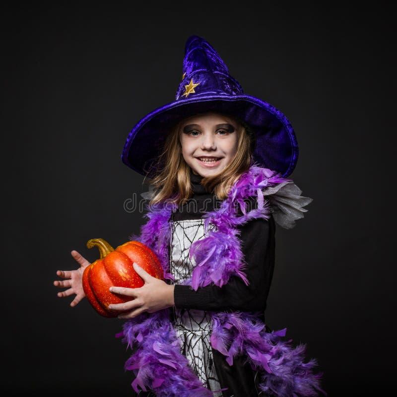 Pequeña bruja linda de Halloween que sostiene una calabaza anaranjada foto de archivo