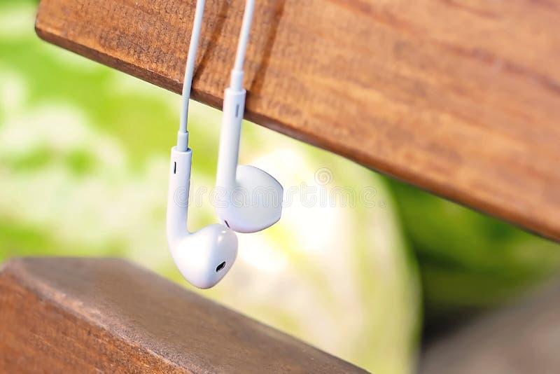 Pequeña caída blanca de los auriculares en el banco El concepto de tecnología y de naturaleza imagenes de archivo