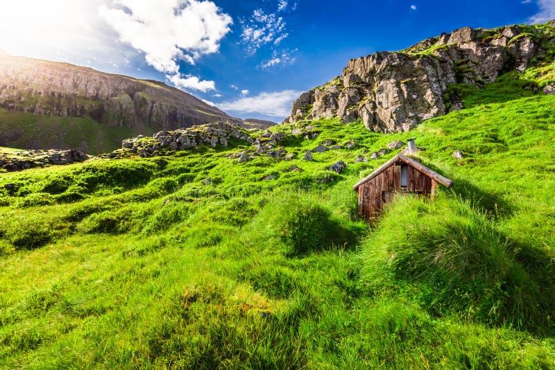 Pequeña cabaña de la montaña en la colina herbosa, Islandia fotografía de archivo