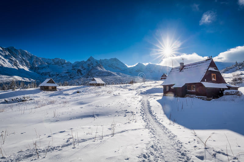 Pequeña cabaña de la montaña en valle del invierno en la puesta del sol imagen de archivo
