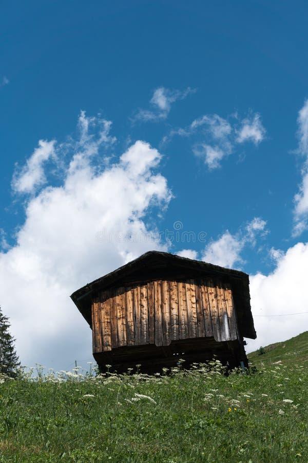Pequeña cabaña de madera en medio un paisaje idílico de la montaña en Suiza fotografía de archivo