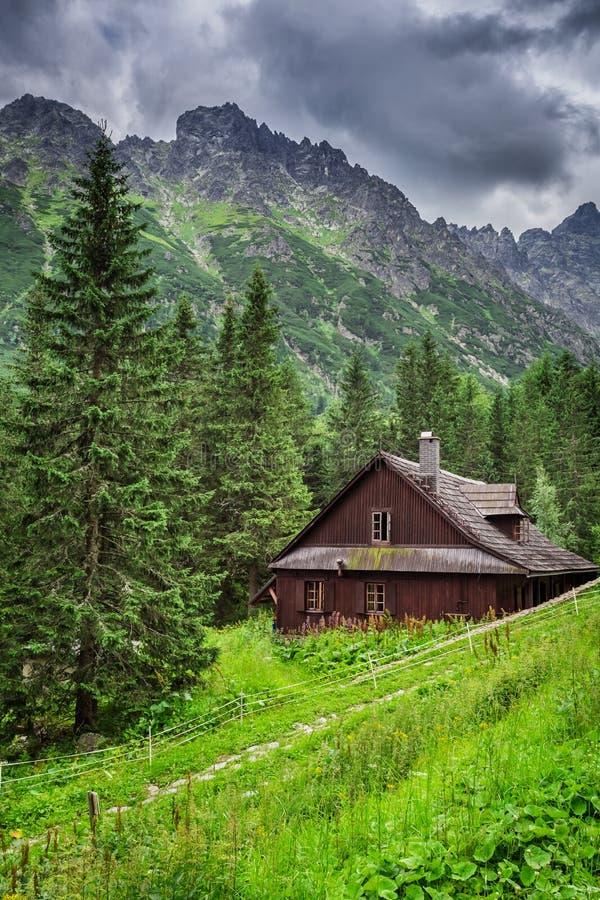 Pequeña cabaña en el medio de las montañas fotografía de archivo