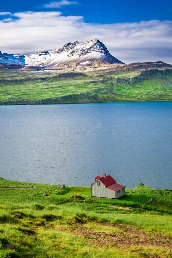 Pequeña cabaña en las montañas sobre el fiordo, Islandia fotografía de archivo