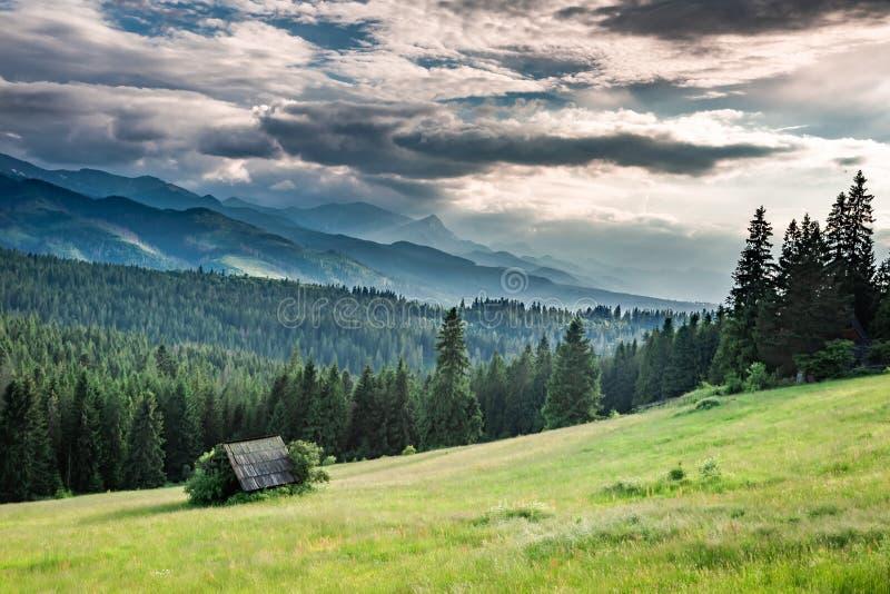 Pequeña cabaña hermosa en el valle verde en la puesta del sol, montañas de Tatra foto de archivo libre de regalías