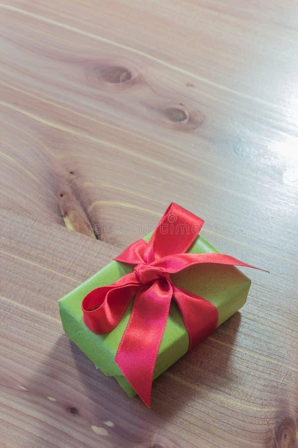 Pequeña caja de regalo, verde con la cinta de satén roja grande, diagonal, fondo de madera neutral imagen de archivo