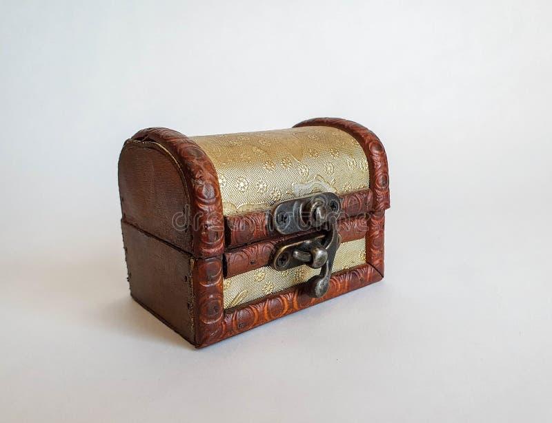 Pequeña caja del pecho de la vieja moda de oro de madera, caja del tesoro en el fondo natural blanco fotografía de archivo libre de regalías