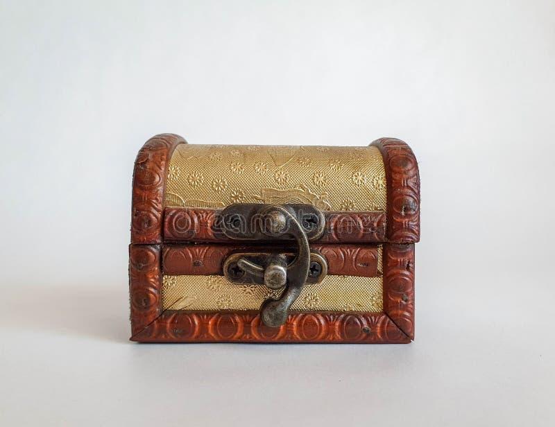 Pequeña caja del pecho de la vieja moda de oro de madera, caja del tesoro en el fondo natural blanco, no imágenes de archivo libres de regalías
