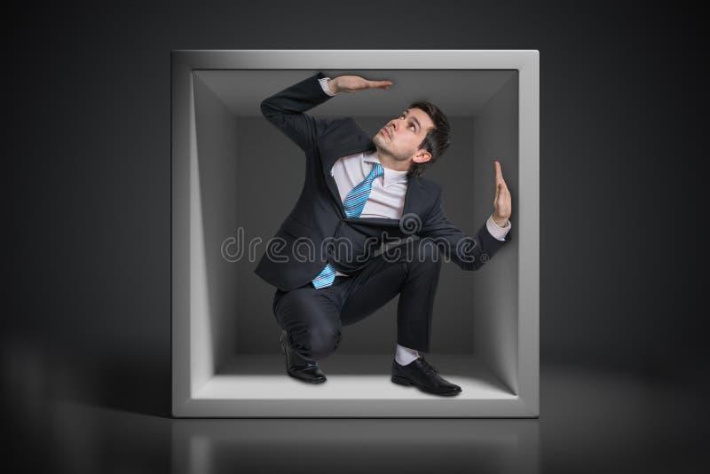 Pequeña caja incómoda interior atrapada hombre de negocios joven foto de archivo