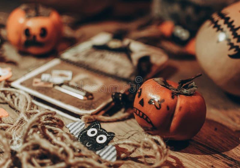 Pequeña calabaza de Halloween con caras pintadas en el suelo de madera, al lado hay un cuaderno con murciélagos, trabajo hecho a imagen de archivo libre de regalías
