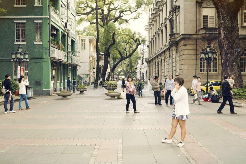 Pequeña calle de la ciudad con los peatones, gente que camina en calle urbana adentro en el centro de la ciudad, opinión de la ca foto de archivo libre de regalías