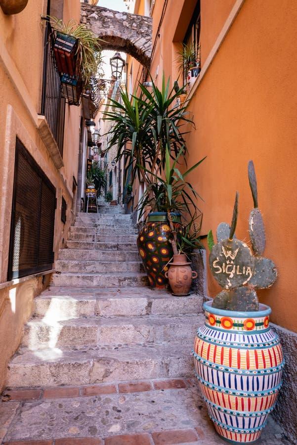 Pequeña calle de la ciudad de Taormina y cactus con la palabra SICILIA Sicilia, Italia foto de archivo libre de regalías