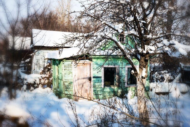 Pequeña casa abandonada en la nieve fotos de archivo