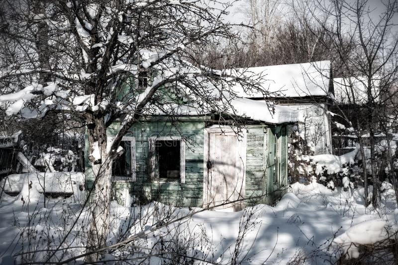 Pequeña casa abandonada en la nieve imagen de archivo libre de regalías