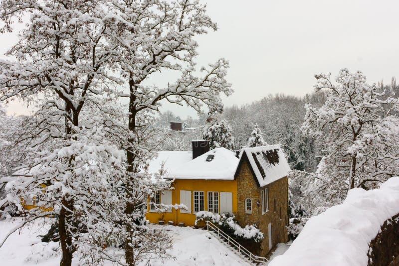 Pequeña casa amarilla acogedora en el bosque Alemania del invierno foto de archivo