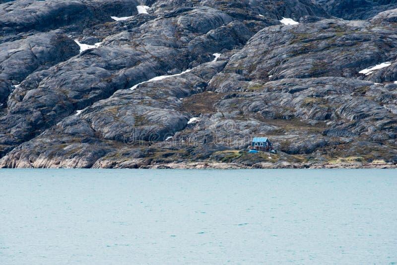 Pequeña casa azul minúscula en medio de la nada, fiordo de Semilinguaq, Groenlandia imagen de archivo