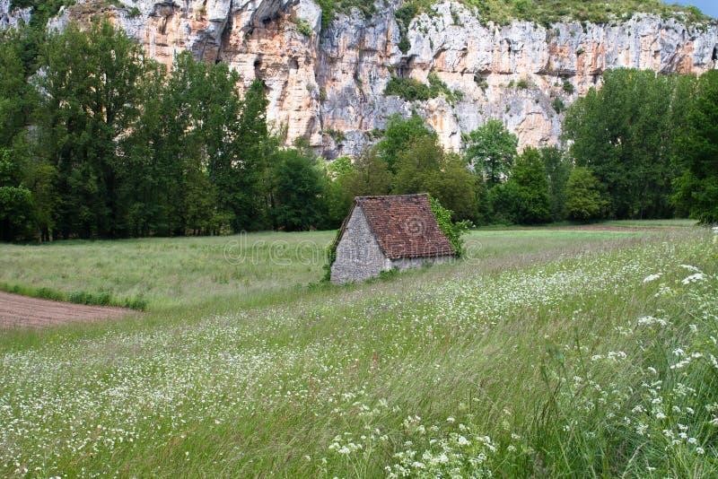 Pequeña casa de piedra hermosa en el medio del campo verde floreciente en fondo del tiempo de primavera fotos de archivo libres de regalías