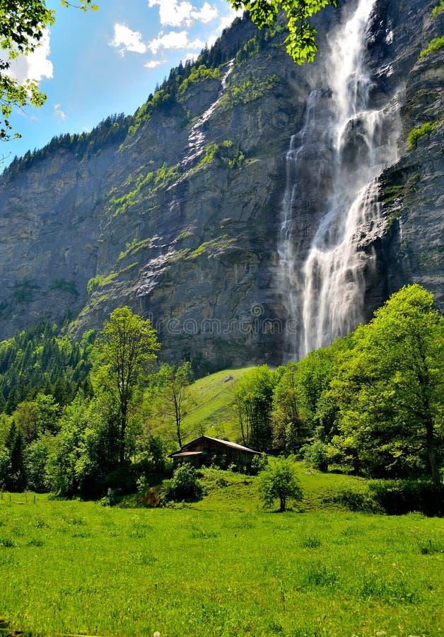 Pequeña casa debajo de una cascada suiza foto de archivo