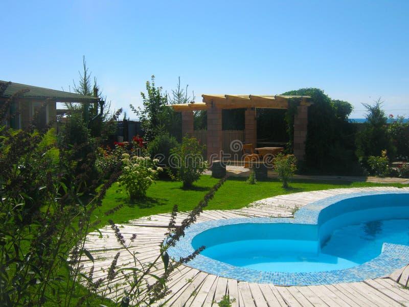 Pequeña casa del jardín de la piscina y del verano fotografía de archivo