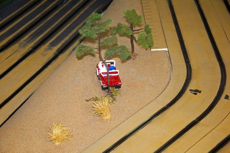 Pequeña casa del juguete, coche rojo, árboles y linterna en la pista del juguete, macro imagen de archivo libre de regalías