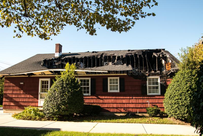 Pequeña casa roja con ella tejado y último piso del ` s destruidos por el fuego imagenes de archivo