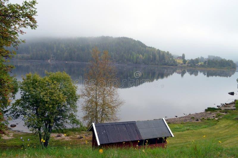 Pequeña casa roja en Noruega en un lago imágenes de archivo libres de regalías