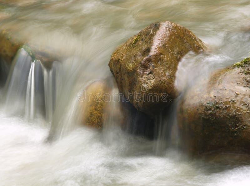 Pequeña cascada en el río de la montaña Fondo natural hermoso de piedras y con agua que fluye, que empaña y hacer espuma fotografía de archivo