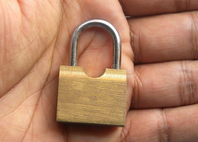 Pequeña cerradura de cobre amarillo del metal en la palma de la mano fotografía de archivo libre de regalías