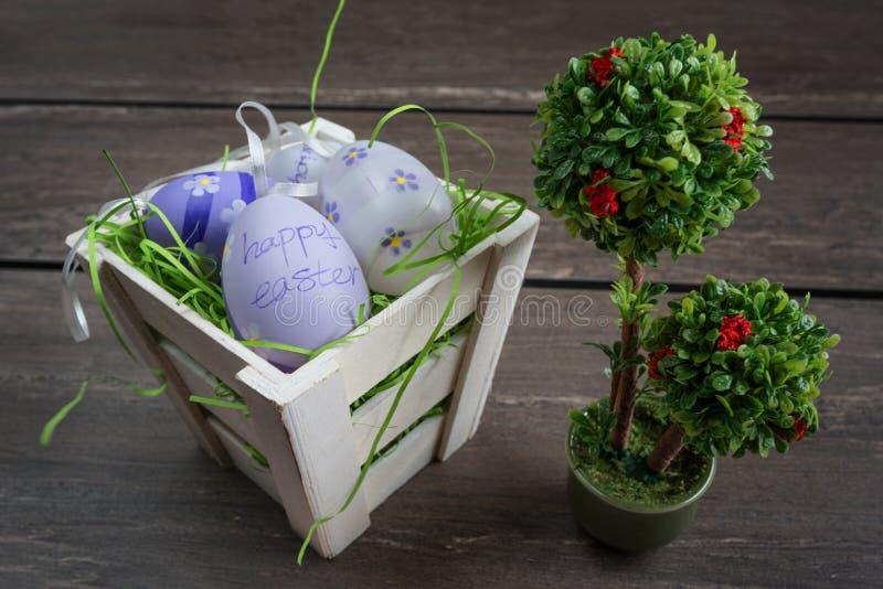 Pequeña cesta de Pascua con huevos coloreados y un pequeño bonsai en el tablero de madera gris fotos de archivo