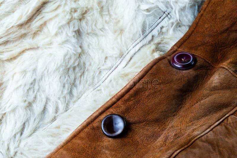 Pequeña chaqueta gruesa marrón del seude con la piel de las ovejas blancas que alinea textura del primer con el foco selectivo y  foto de archivo libre de regalías