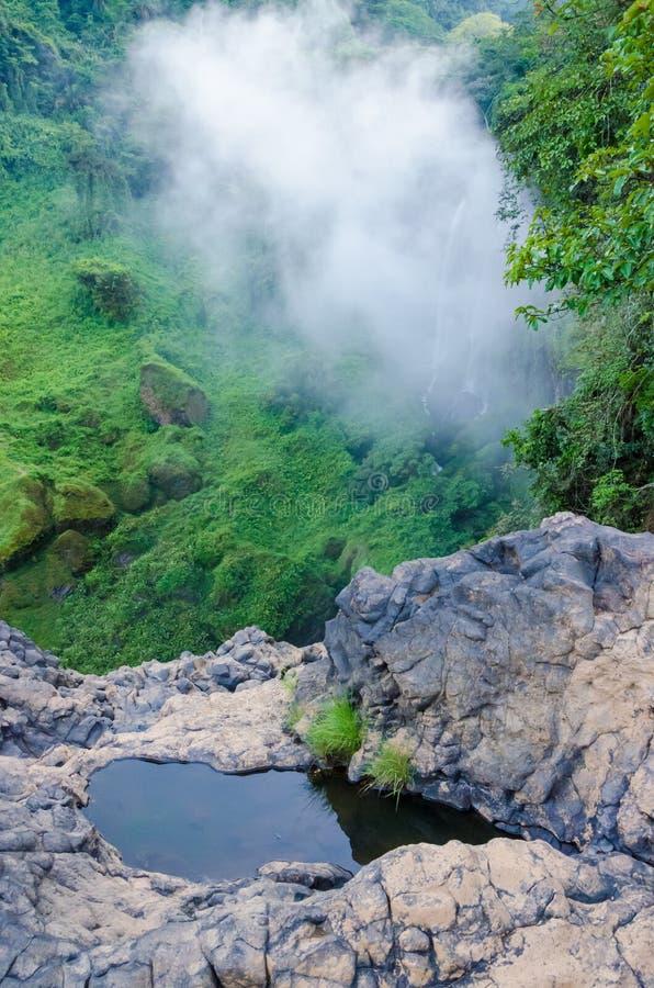 Pequeña charca de la roca en la selva tropical del Camerún, África con la nube brumosa, el verde enorme y cascadas en fondo fotografía de archivo