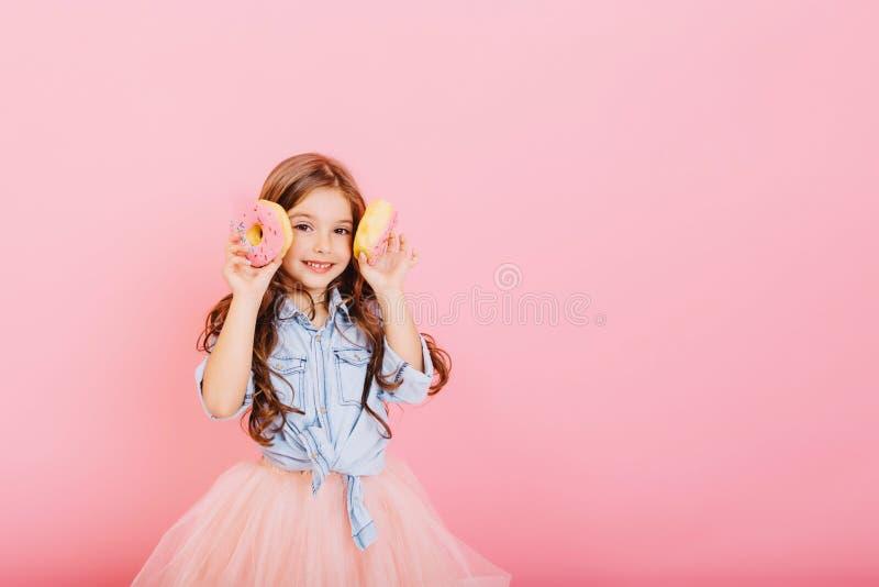 Pequeña chica linda con el pelo largo de la morena divirtiéndose en cámara con donuts aislados en fondo rosa. charming imagenes de archivo