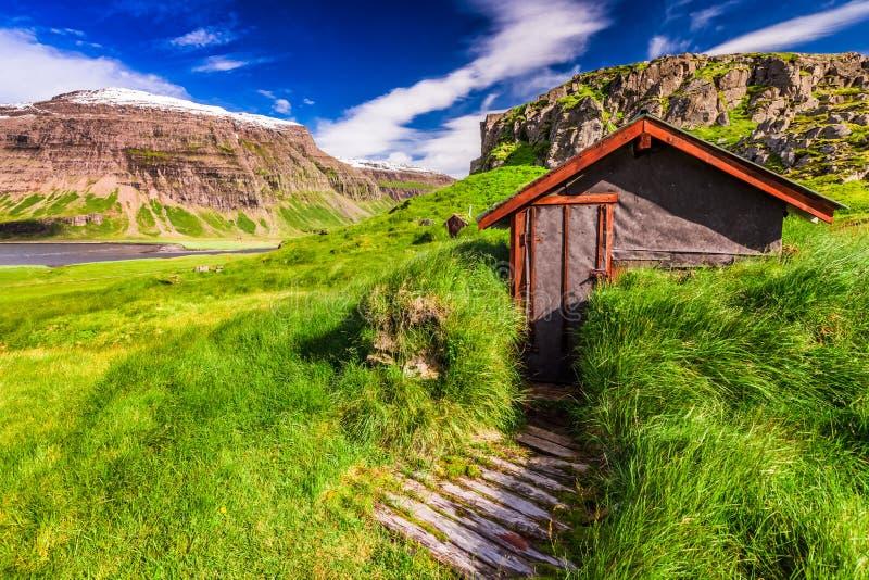 Pequeña choza de la montaña en la colina herbosa verde, Islandia fotografía de archivo libre de regalías