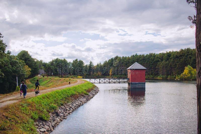 Pequeña choza roja empleada un río y conectada con un puente con sorprender paisaje natural fotografía de archivo libre de regalías