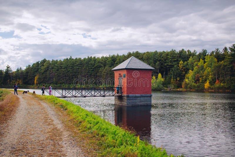 Pequeña choza roja empleada un río y conectada con un puente con sorprender paisaje natural imagen de archivo
