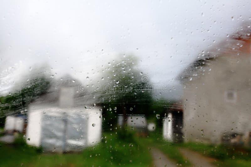Pequeña ciudad a través de la ventana lluviosa fotos de archivo libres de regalías