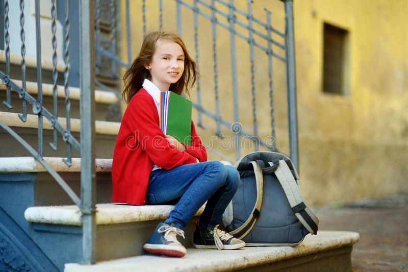 Pequeña colegiala adorable que estudia al aire libre en día brillante del otoño Estudiante joven que hace su preparación Educació imágenes de archivo libres de regalías