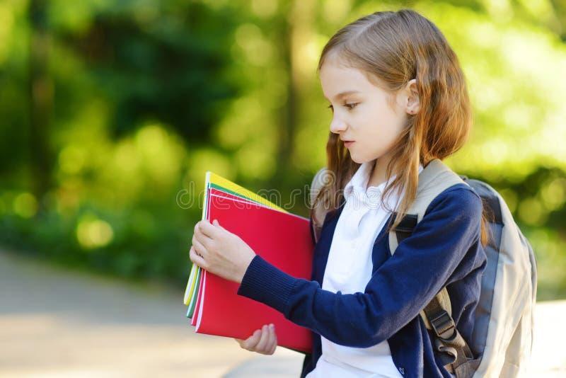 Pequeña colegiala adorable que estudia al aire libre en día brillante del otoño Estudiante joven que hace su preparación Educació fotografía de archivo