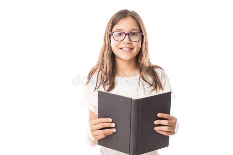 Pequeña colegiala linda con los vidrios que llevan de un libro, ov aislado foto de archivo