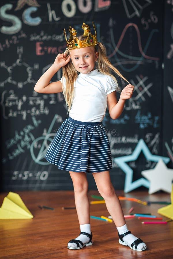 Pequeña colegiala linda contra la pizarra con fórmulas de la escuela, con una corona del oro en su cabeza fotos de archivo