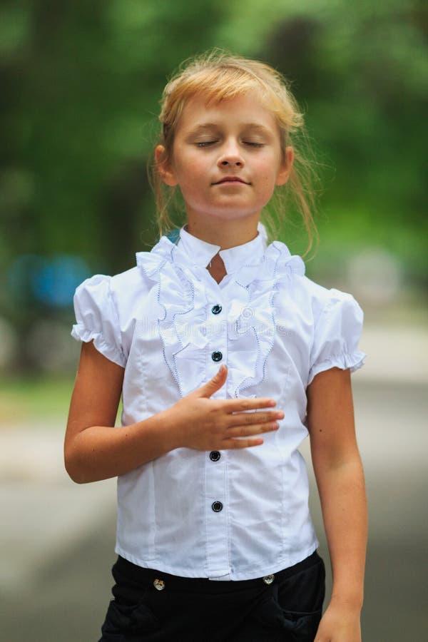 Pequeña colegiala linda patriótica en uniforme escolar que escucha el himno nacional fotos de archivo