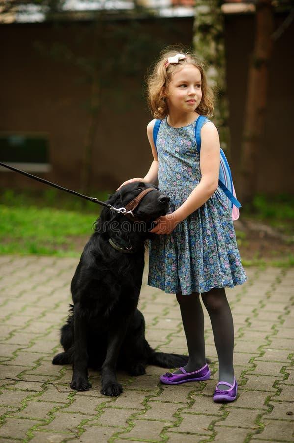 Pequeña colegiala que acaricia un perro negro grande que se sienta en un correo fotografía de archivo