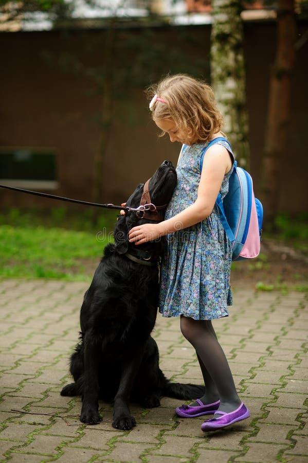 Pequeña colegiala que acaricia un perro negro grande que se sienta en un correo imagenes de archivo