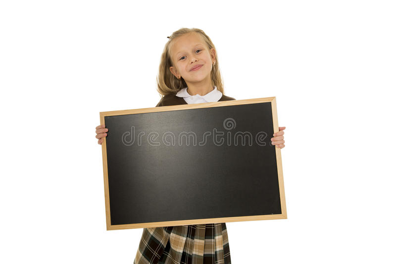 Pequeña colegiala rubia hermosa que sonríe pequeña pizarra en blanco feliz y alegre de la tenencia y de la demostración fotos de archivo