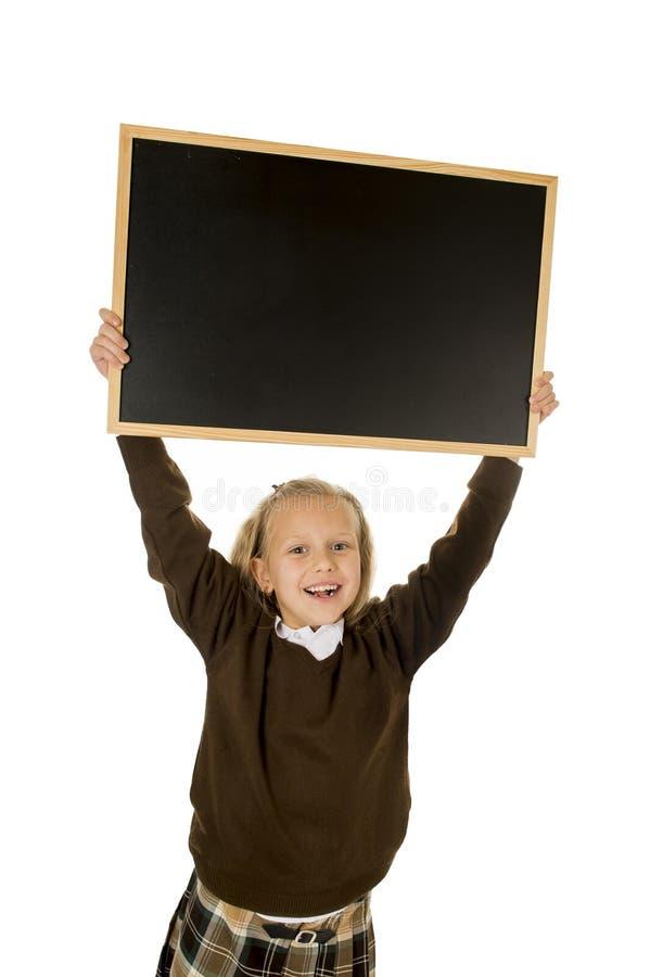 Pequeña colegiala rubia hermosa que sonríe pequeña pizarra en blanco feliz y alegre de la tenencia y de la demostración foto de archivo libre de regalías