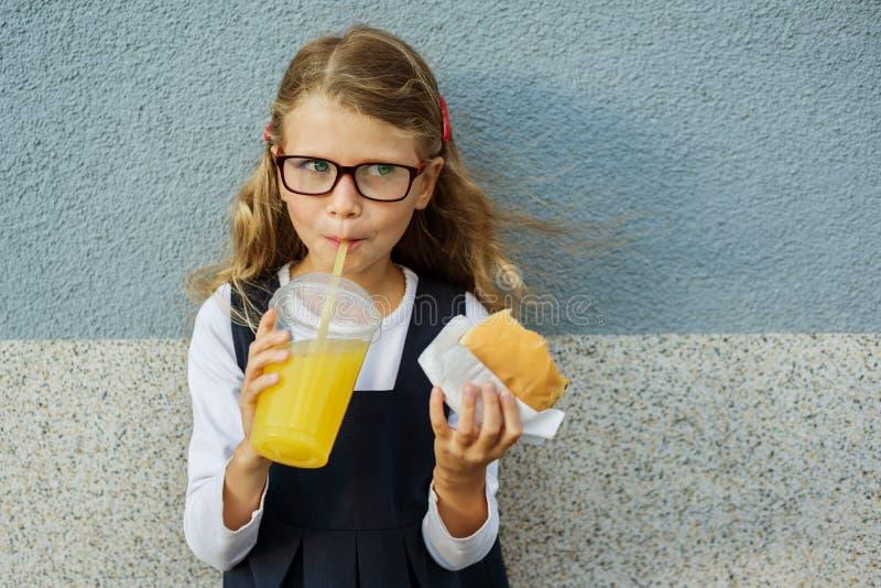 Pequeña colegiala sonriente linda que sostiene una hamburguesa y una naranja imagenes de archivo