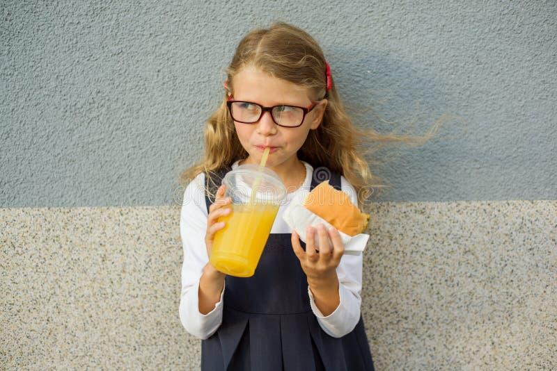 Pequeña colegiala sonriente linda que sostiene una hamburguesa y una naranja foto de archivo