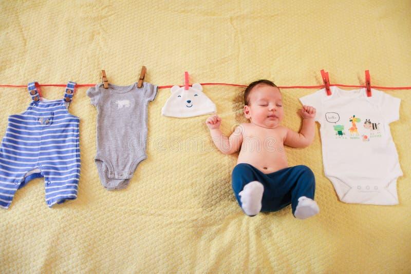 Pequeña ejecución linda del bebé con ropa en cuerda imagen de archivo
