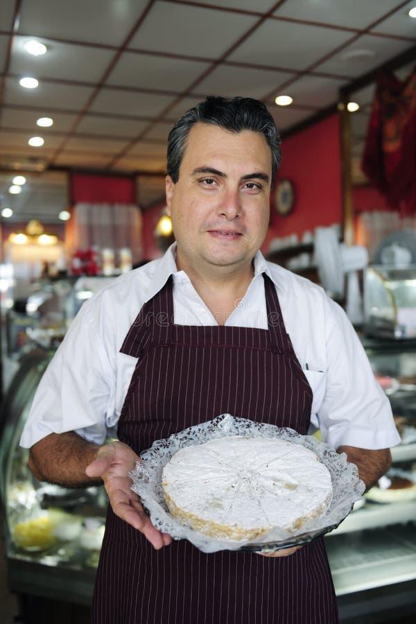Pequeña empresa: camarero que muestra una torta sabrosa fotos de archivo libres de regalías