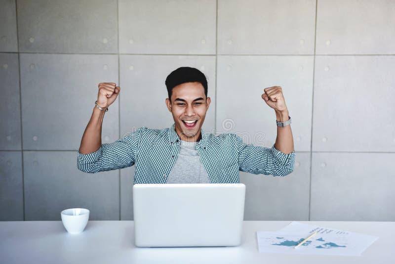 Pequeña empresa y concepto acertado Hombre de negocios asiático joven Glad para recibir buenas noticias imagen de archivo