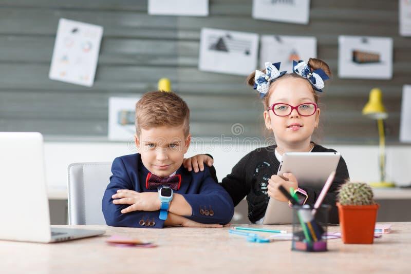 Pequeña empresaria que abraza su ordenador portátil en el lugar de trabajo foto de archivo